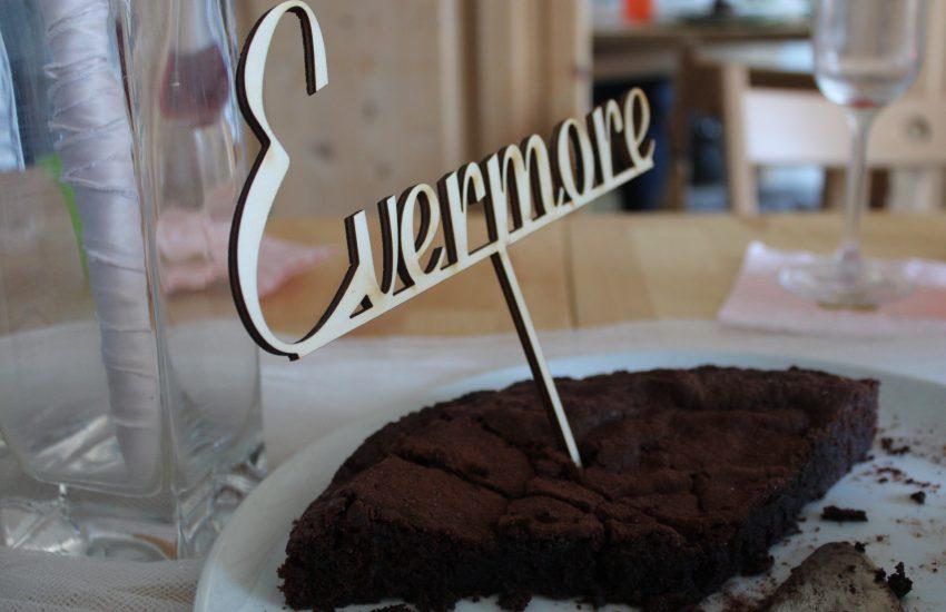 Coronahochzeit: Ein Kuchen mit einem Cake-Topper auf dem Evermore steht