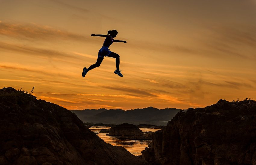 Women jumps over a ravine