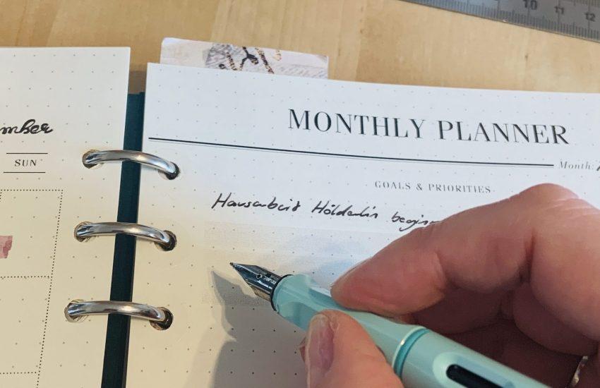 Darstellung eins Monthly Planers im Ringbuch Filofax Clipbook: Hand schreibt mit Füller etwas auf ein Blatt Papier