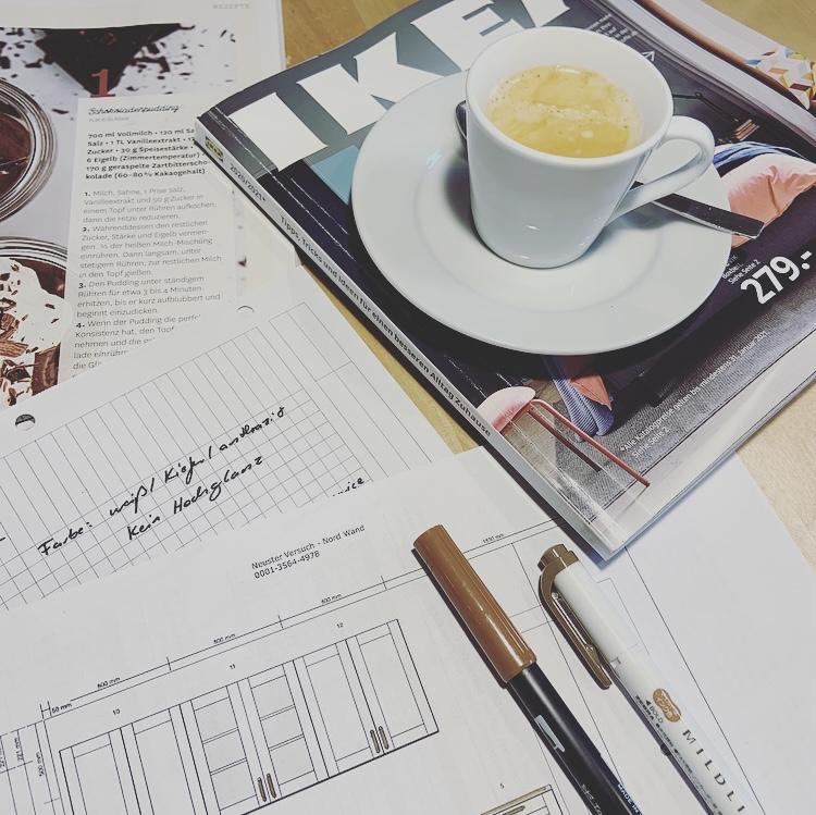 Eine Espressotasse steht auf einem Möbelkatalog. Daneben liegen Notizen zu einer Küchenplanung