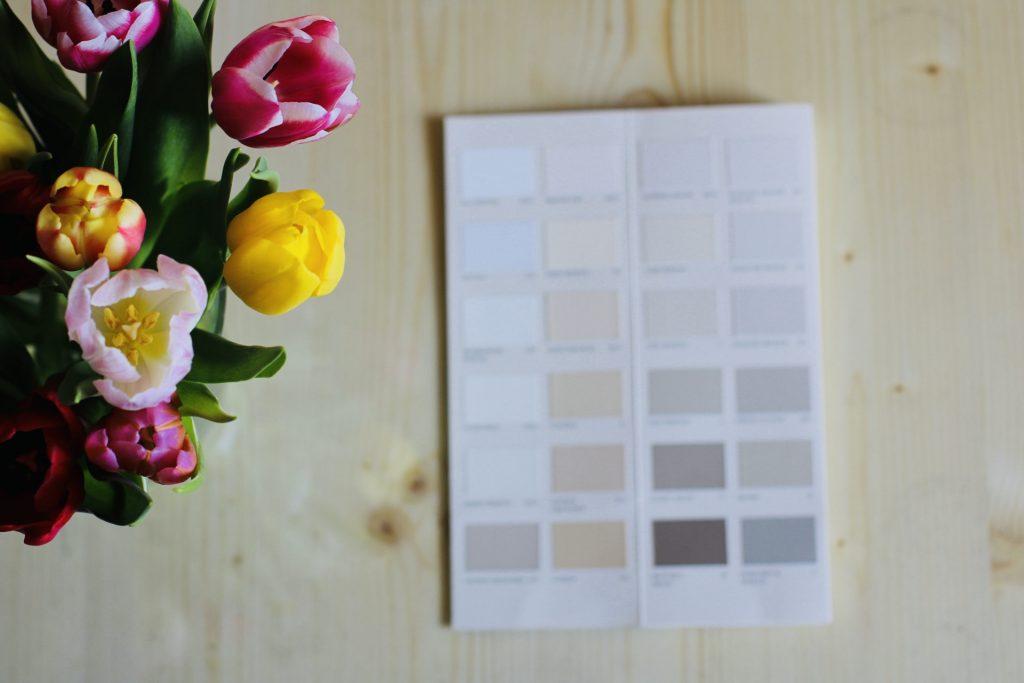 ein Strauß bunter Tulpen, daneben lief eine aufgeschlagene Farbpalette für Wandfarben